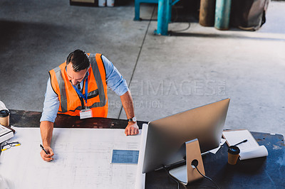 Buy stock photo High angle shot of a male engineer working on blueprints while making use of a computer inside of a workshop