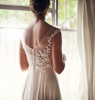Buy stock photo Shot of a young bride looking out of her window on her wedding day