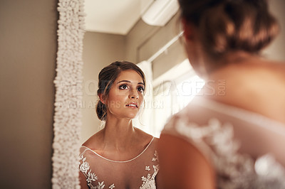 Buy stock photo Shot of a beautiful young bride looking at herself in the mirror on her wedding day