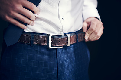 Buy stock photo Cropped shot of a man wearing a belt with his jeans and shirt on his wedding day