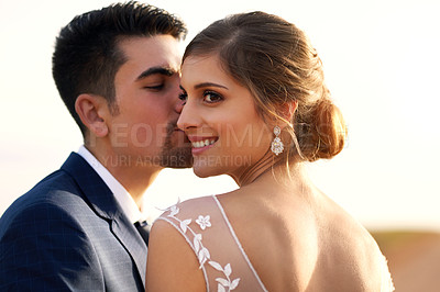Buy stock photo Shot of a happy young couple kissing outside on their wedding day
