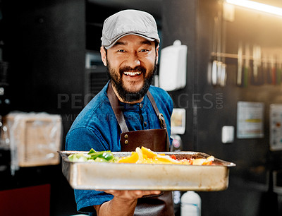 Buy stock photo Portrait of a cheerful young chef holding a platter of delicious food inside the kitchen in his cafe