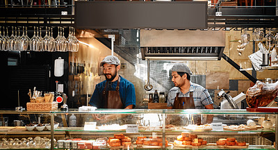 Buy stock photo Shot of two young barista's preparing a meal and working together inside a cafe