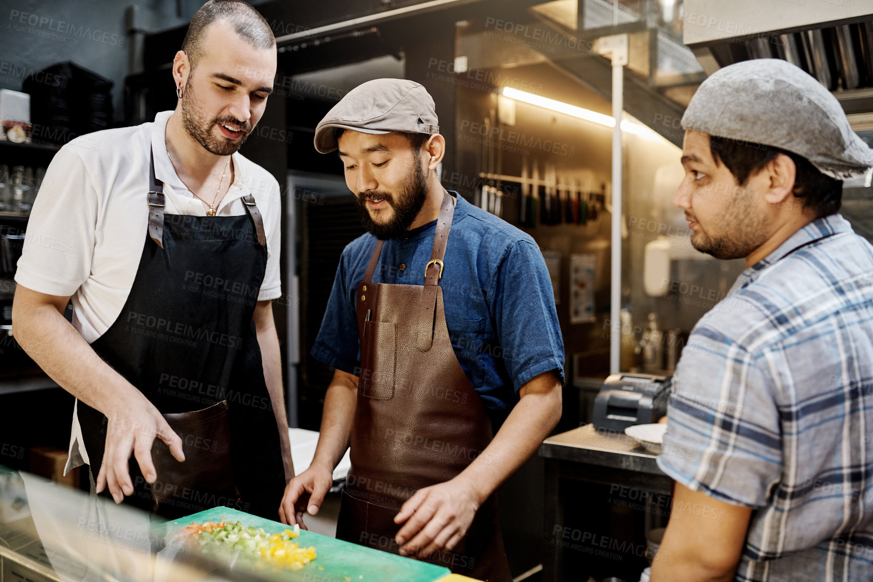 Buy stock photo Shot of three young cooks preparing a meal inside the kitchen of a cafe
