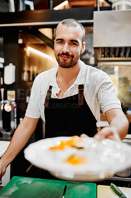 Buy stock photo Portrait of a handsome young barista serving a plate of food to a customer inside a cafe