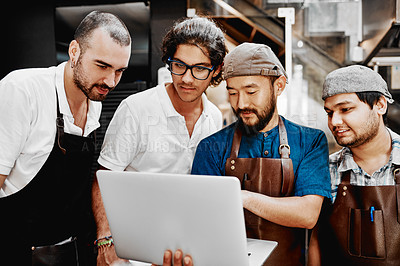 Buy stock photo Shot of a group of young barista's and their manager using a laptop inside a cafe