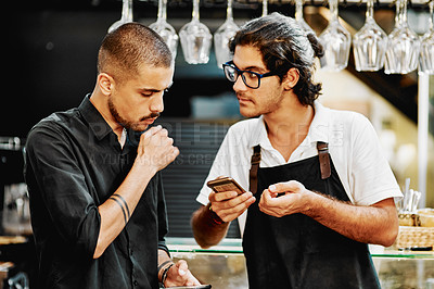 Buy stock photo Shot of a handsome young businessman and a barista using a cellphone inside a cafe