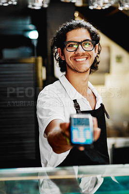 Buy stock photo Portrait of handsome young barista holding a card machine inside a cafe