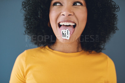 Buy stock photo Studio shot of an attractive young woman posing with a piece of paper with the word