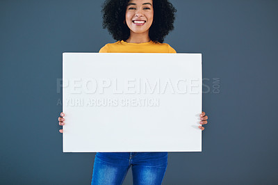 Buy stock photo Studio portrait of an attractive young woman holding a blank placard while standing against a grey background