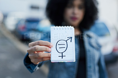 Buy stock photo Shot of an unrecognizable woman holding a note pad with gender symbols drawn on it in the city