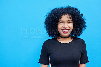 Buy stock photo Portrait of an attractive young woman posing against a blue background