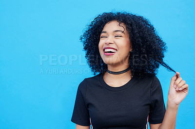 Buy stock photo Shot of an attractive young woman pulling her hair against a blue background