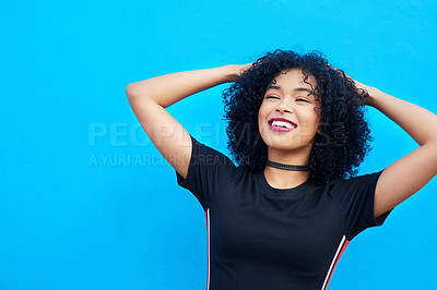 Buy stock photo Shot of an attractive young woman holding her hair against a blue background