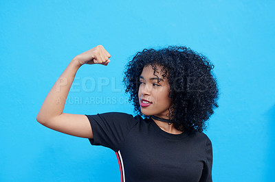 Buy stock photo Shot of an attractive young flexing her biceps against a blue background