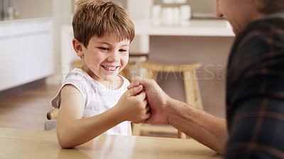 Buy stock photo Shot of an adorable little boy thumb wrestling and playing with his father at home