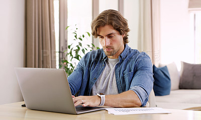 Buy stock photo Shot of a handsome young businessman using a laptop while going over paperwork and his finances at home