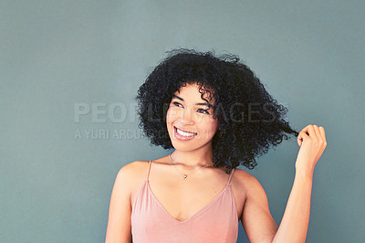 Buy stock photo Portrait of a beautiful young woman pulling her hair against a grey background