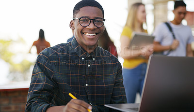 Buy stock photo Portrait of a cheerful young student working on his laptop while waiting to go to class outside of a school