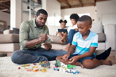 Buy stock photo Shot of a father and son playing with toys during family time at home