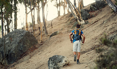 Buy stock photo Shot of a man wearing a backpack while out hiking