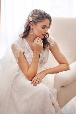 Buy stock photo Cropped shot of an attractive young bride sitting alone in the dressing room and looking contemplative before her wedding