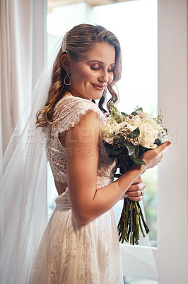 Buy stock photo Cropped shot of an attractive young bride standing alone in the dressing room and holding her bouquet of flowers