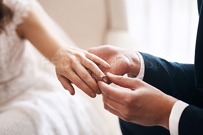 Buy stock photo Cropped shot of an unrecognizable groom putting a diamond ring on his wife's finger during their wedding