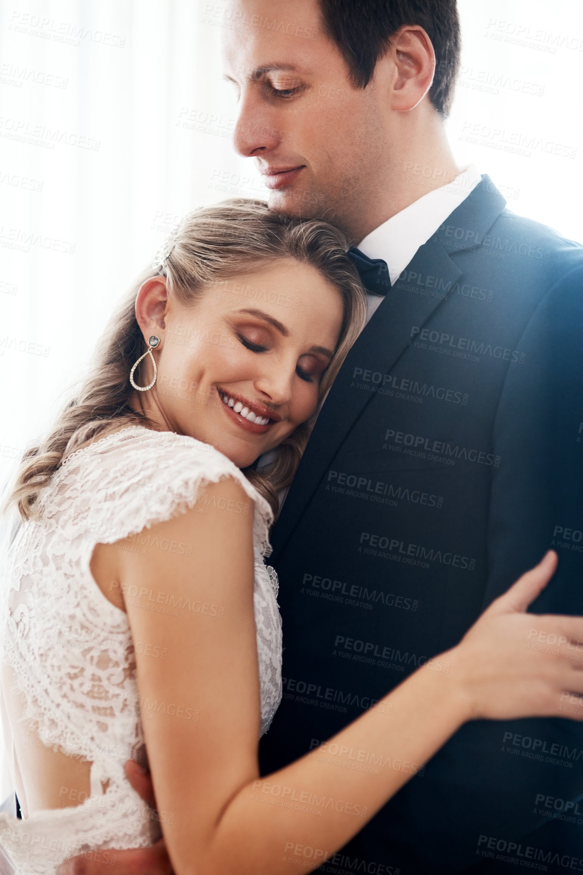 Buy stock photo Cropped shot of a happy young couple standing indoors and hugging each other affectionately after their wedding