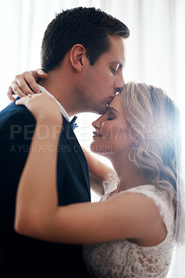Buy stock photo Cropped shot of a handsome young groom affectionately kissing his wife on the forehead after their wedding