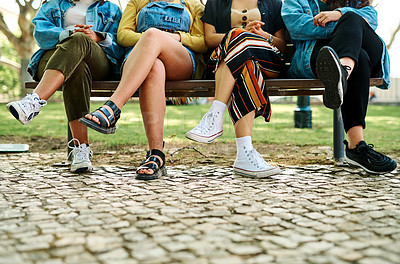 Buy stock photo Cropped shot of an unrecognizable group of students sitting cross legged on a park bench after a study session