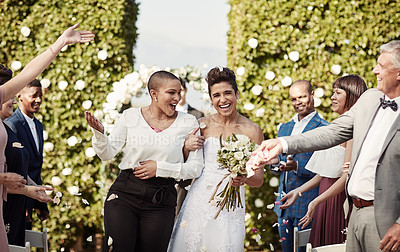 Buy stock photo Cropped shot of a beautiful young lesbian couple leaving their wedding venue with their guests showering them with confetti