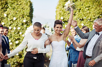Buy stock photo Cropped shot of a beautiful young lesbian bride holding up her bouquet while leaving the wedding venue with her new wife