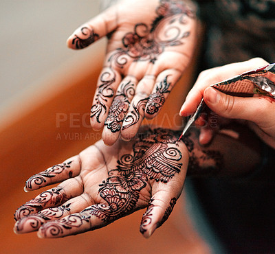 Buy stock photo Cropped shot of an unrecognizable woman getting henna applied to her hands in preparation for her wedding