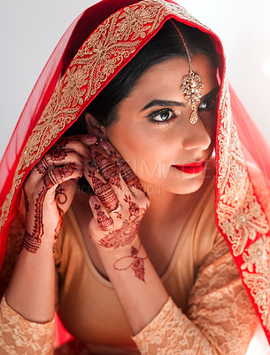 Buy stock photo Shot of a beautiful young woman putting on her earrings in preparation for her wedding