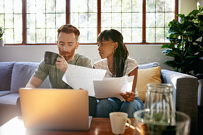 Buy stock photo Shot of a young couple going through paperwork while using a laptop at home