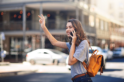 Buy stock photo Cropped shot of an attractive young woman making a phonecall while hailing a taxi out in the city