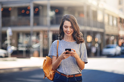 Buy stock photo Cropped shot of an attractive young woman sending text messages while spending her day out in the city