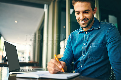 Buy stock photo Cropped shot of a handsome young businessman sitting in a cafe alone and writing in a notebook