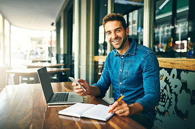 Buy stock photo Cropped portrait of a handsome young businessman sitting alone and making notes while using his cellphone in a cafe