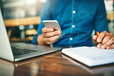 Buy stock photo Cropped shot of an unrecognizable businessman sitting alone and making notes while using his cellphone in a cafe