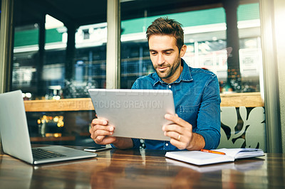 Buy stock photo Cropped shot of a handsome young businessman sitting alone in a cafe and using a tablet