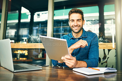 Buy stock photo Cropped portrait of a handsome young businessman sitting alone in a cafe and using a tablet