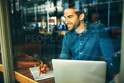 Buy stock photo Cropped shot of a handsome young businessman sitting alone and working in a cafe during the day