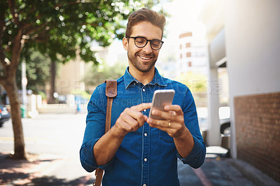 Buy stock photo Shot of a handsome man using his cellphone while out in the city