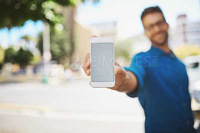 Buy stock photo Shot of a man showing his cellphone while standing outside