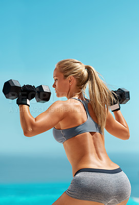 Buy stock photo Cropped shot of a beautiful young woman exercising with dumbbells outdoors