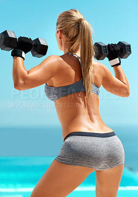 Buy stock photo Rearview shot of an unrecognizable young woman exercising with dumbbells outdoors