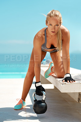 Buy stock photo Full length portrait of a beautiful young woman exercising with a kettle bell on a bench outdoors