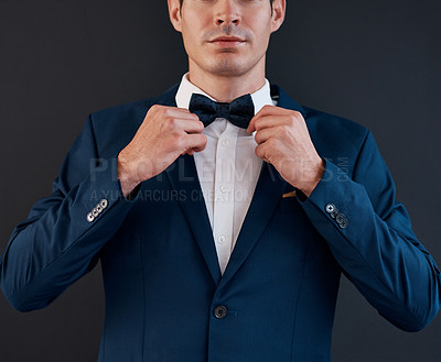 Buy stock photo Cropped shot of an unrecognizable bridegroom adjusting his bowtie in preparation for his wedding